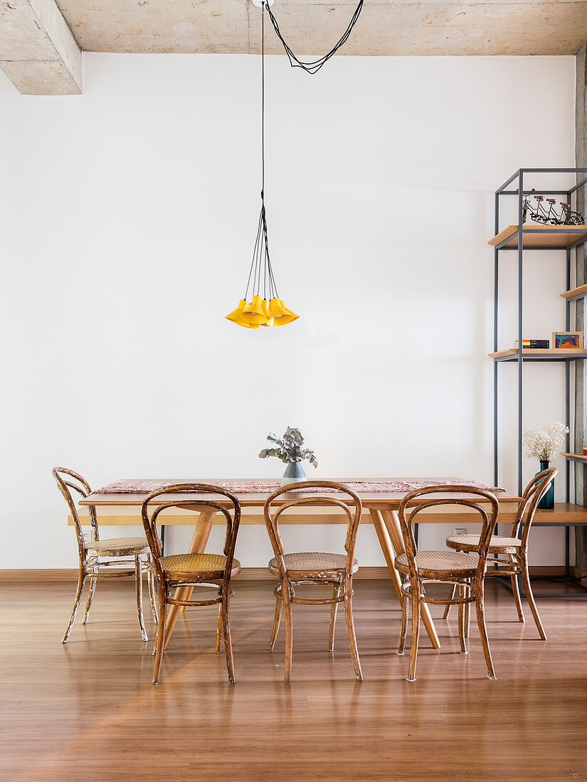 Dining table and bentwood chairs below pendant lamp with small yellow lampshades