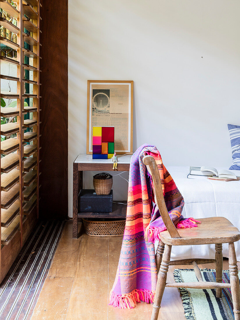 Colourful blanket on rustic wooden chair next to window with louvre blinds