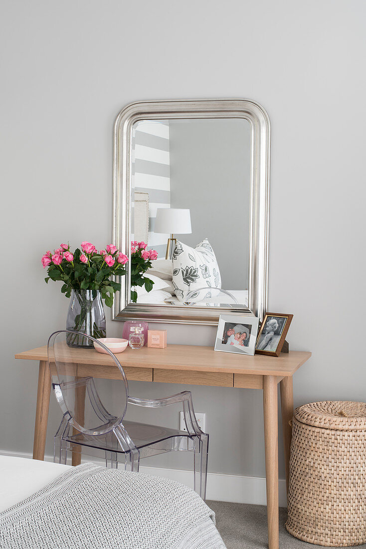 Wooden dressing table, Ghost chair and simple silver-framed mirror