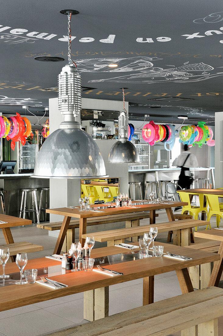 Holztische mit Sitzbänken im Restaurant, im Hintergrund bunte Schwimmreifen über Bartheke