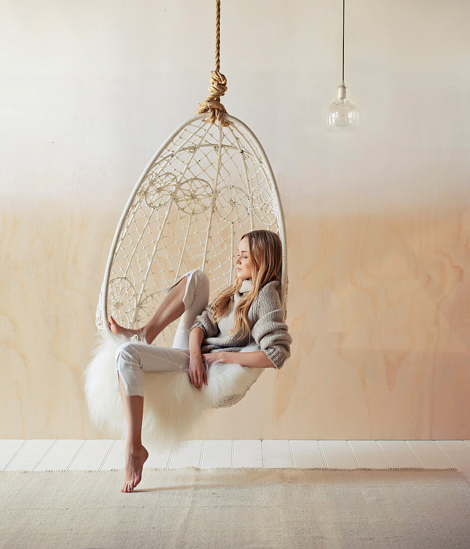 Woman sits relaxed in a boho-style hammock with sheepskin