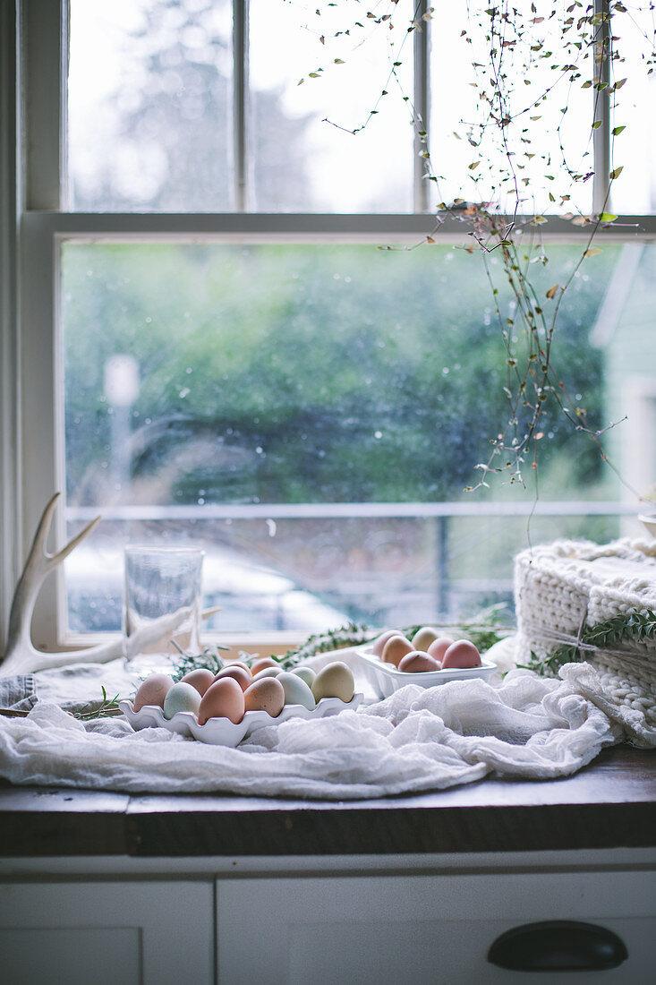 Fresh farm eggs of various colours on kitchen counter next to window