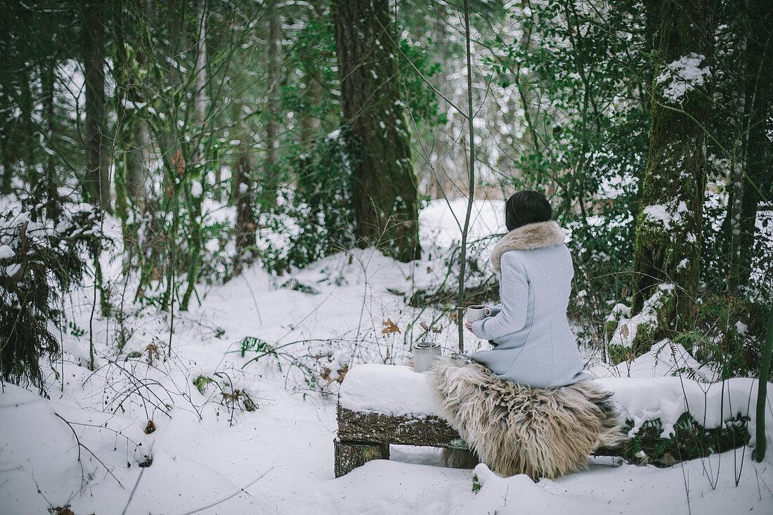 Woman drinking tea in snowy woods
