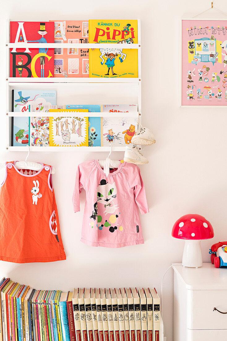 Bookshelves and dresses in bright girl's bedroom