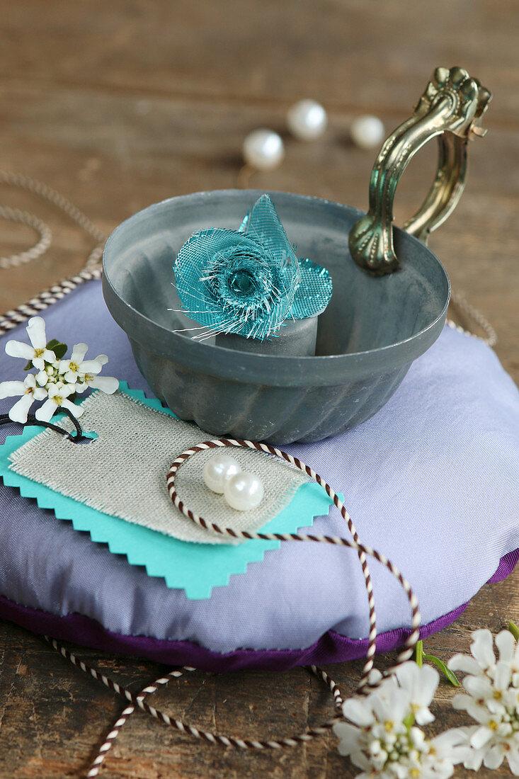 Vintage-style still-life arrangement with bundt-cake tin on round cushion