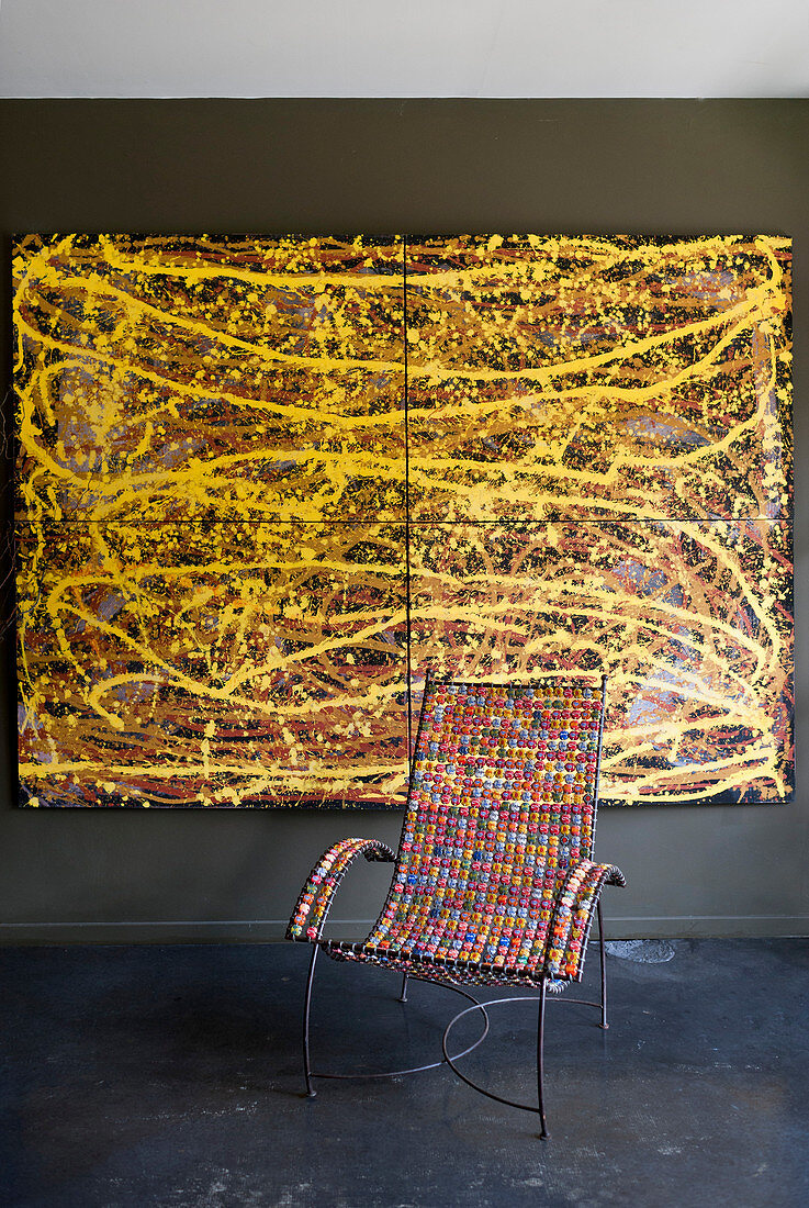 Metal chair with colourful beaded seat and arms in front of painting