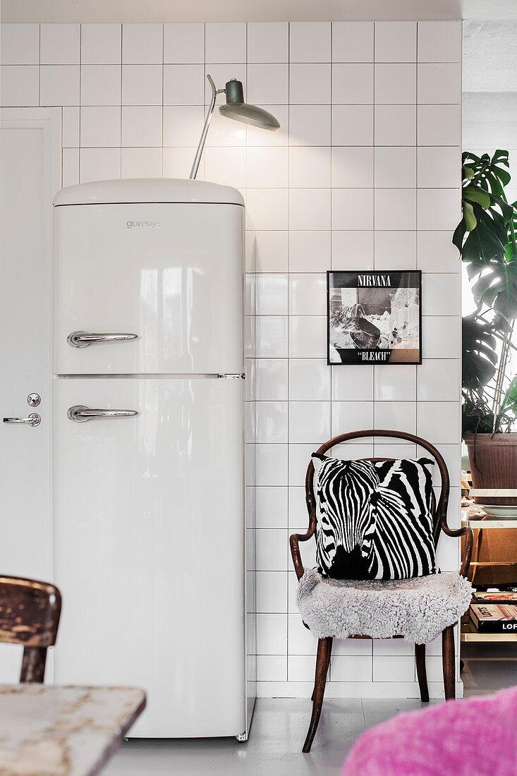 White retro fridge and chair with zebra cushion against white-tiled wall