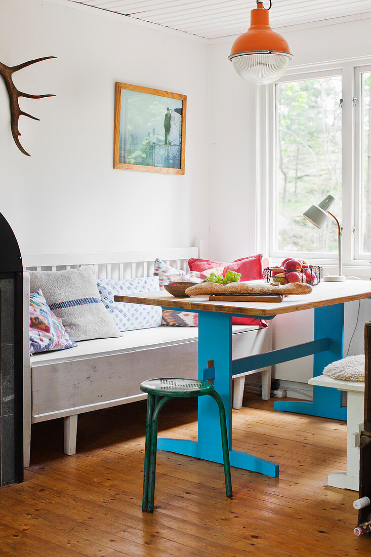 Old wooden table with blue-painted base and bench in kitchen-dining room
