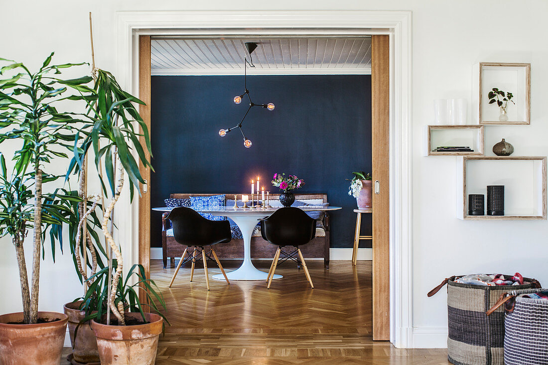 View through open sliding door in dining room with dark wall and classic furniture