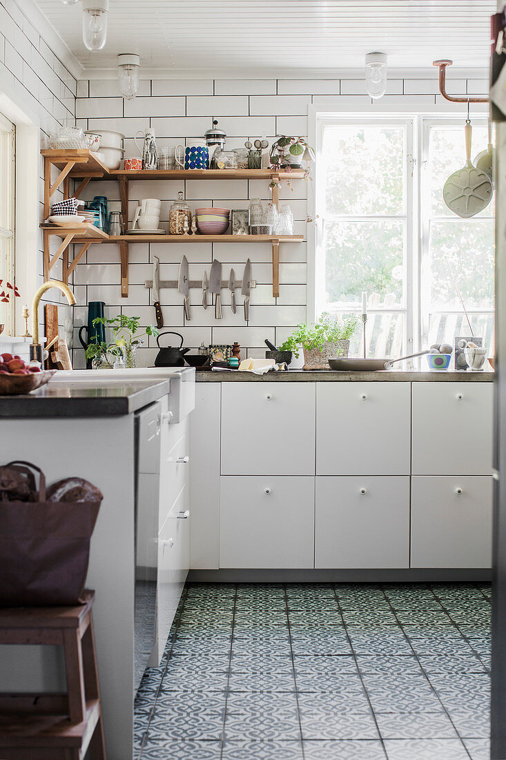 White kitchen counter with concrete worksurfaces and Moroccan tiles on floor