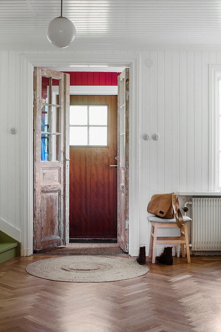 Front door with vestibule in wood-clad hallway