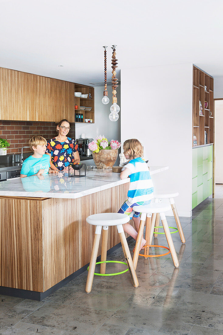 Family around middle block with marble top in open kitchen