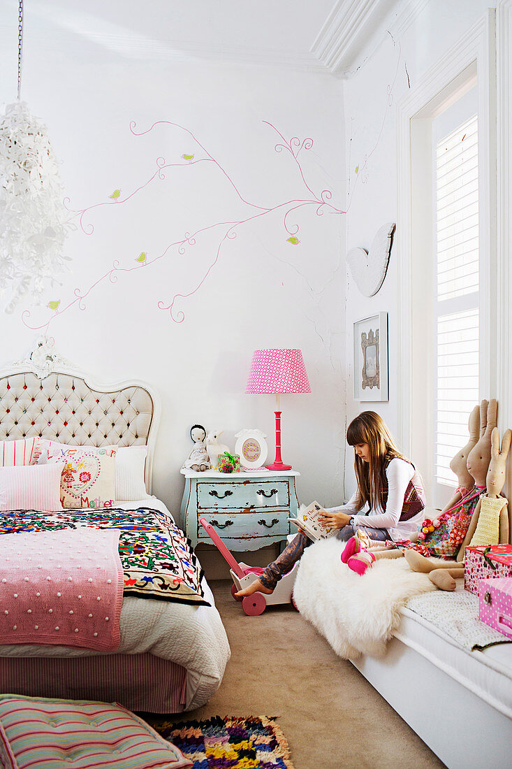 Girl reads on bench with cloth bunny in child's room
