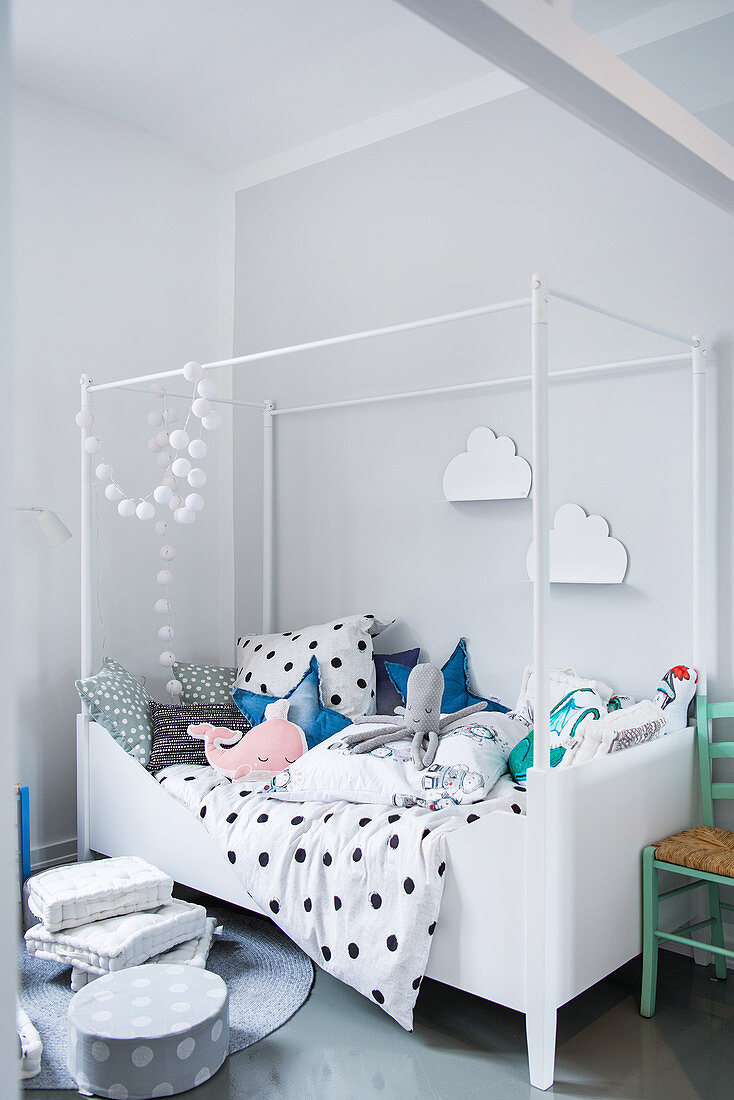 Four-poster bed with polka-dot bed linen and soft toys in bright child's bedroom