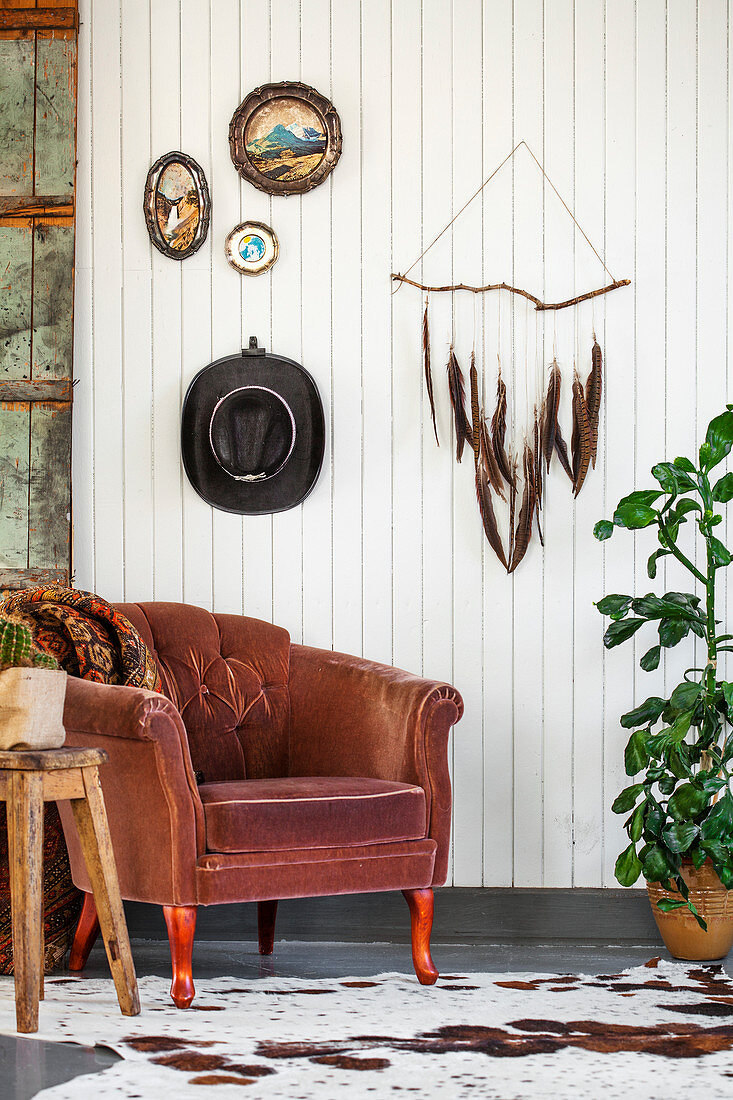 Brown armchair below handmade decorations on white-painted wooden wall
