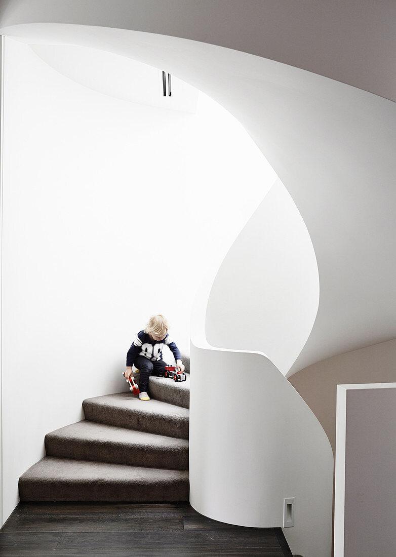 Boy plays on organically shaped, brick stairs