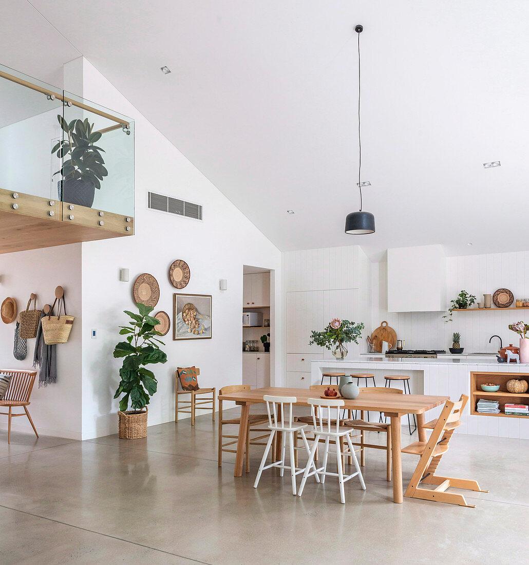 Esstisch im offenen Wohnraum mit Betonboden und Galerie