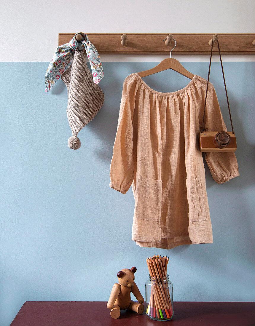 Nudefarbenes Leinenkleid an Hakenleister vor hellblauer Wand