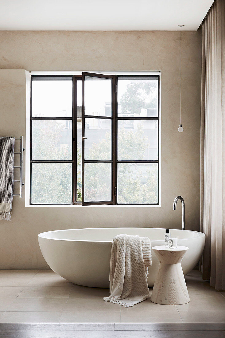 Oval, free-standing bathtub in the bathroom in light gray