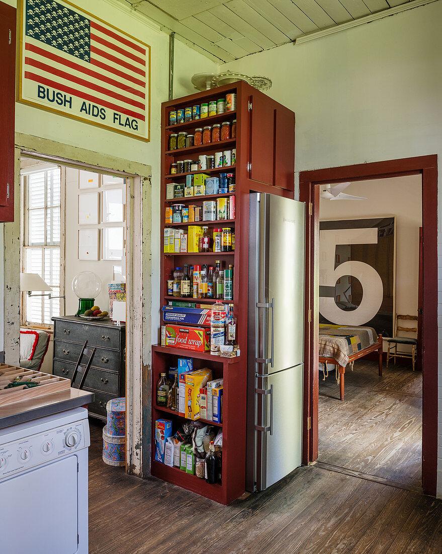 Storage shelves with fridge in corner of kitchen