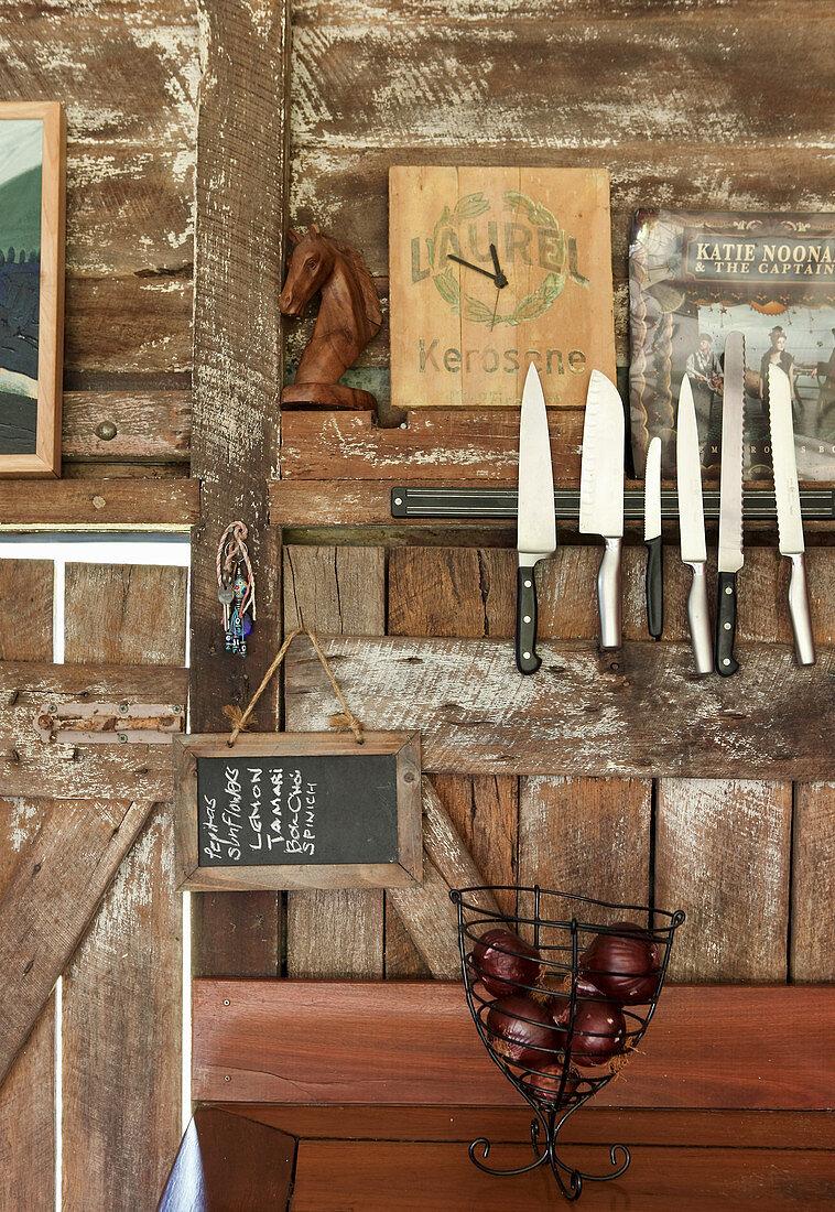 Magnetleiste mit Messern an einer rustikalen Bretterwand