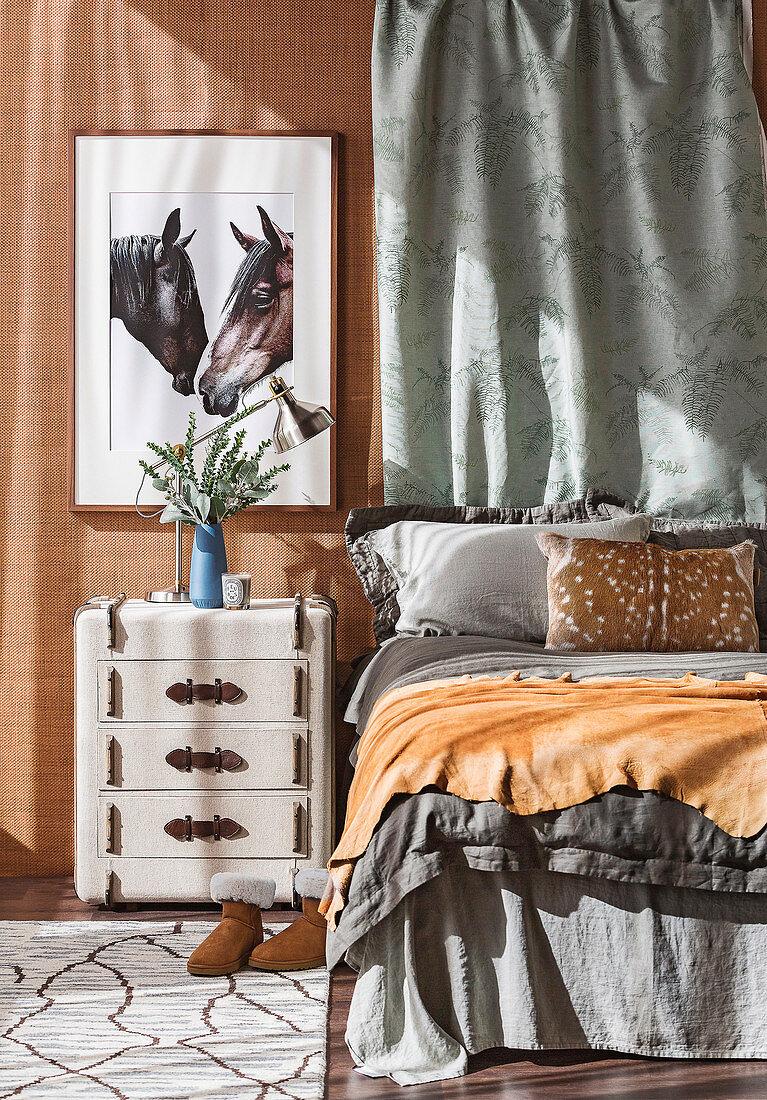 Nachttisch im Koffer-Look, darüber Bild mit Pferdemotiv, Bett mit grauer Bettwösche im Schlafzimmer