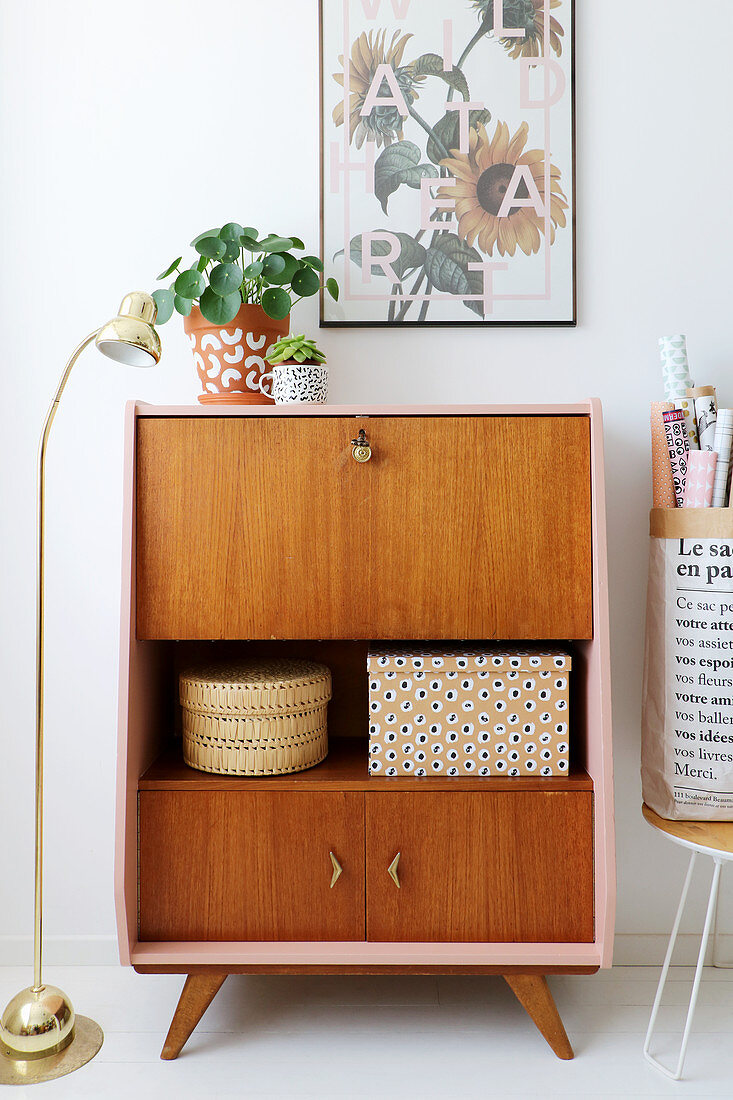 Retro bureau restored and given pink sides and top decorated with house plants and standard lamp