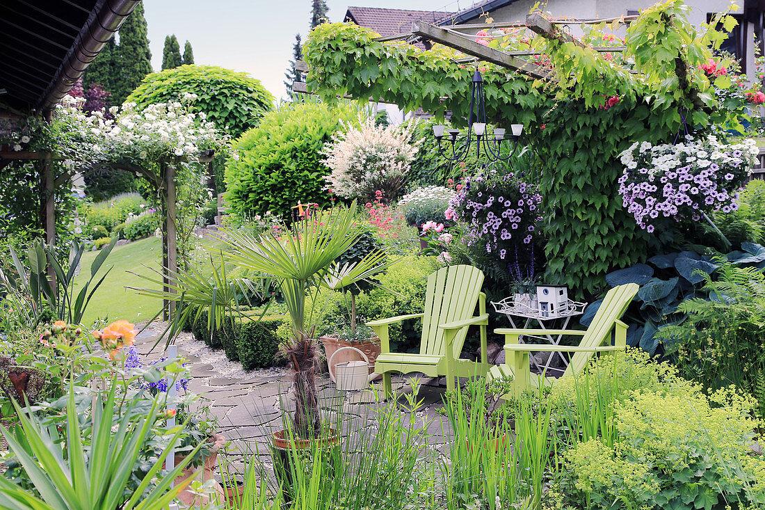 Two green deckchairs on terrace in summery garden