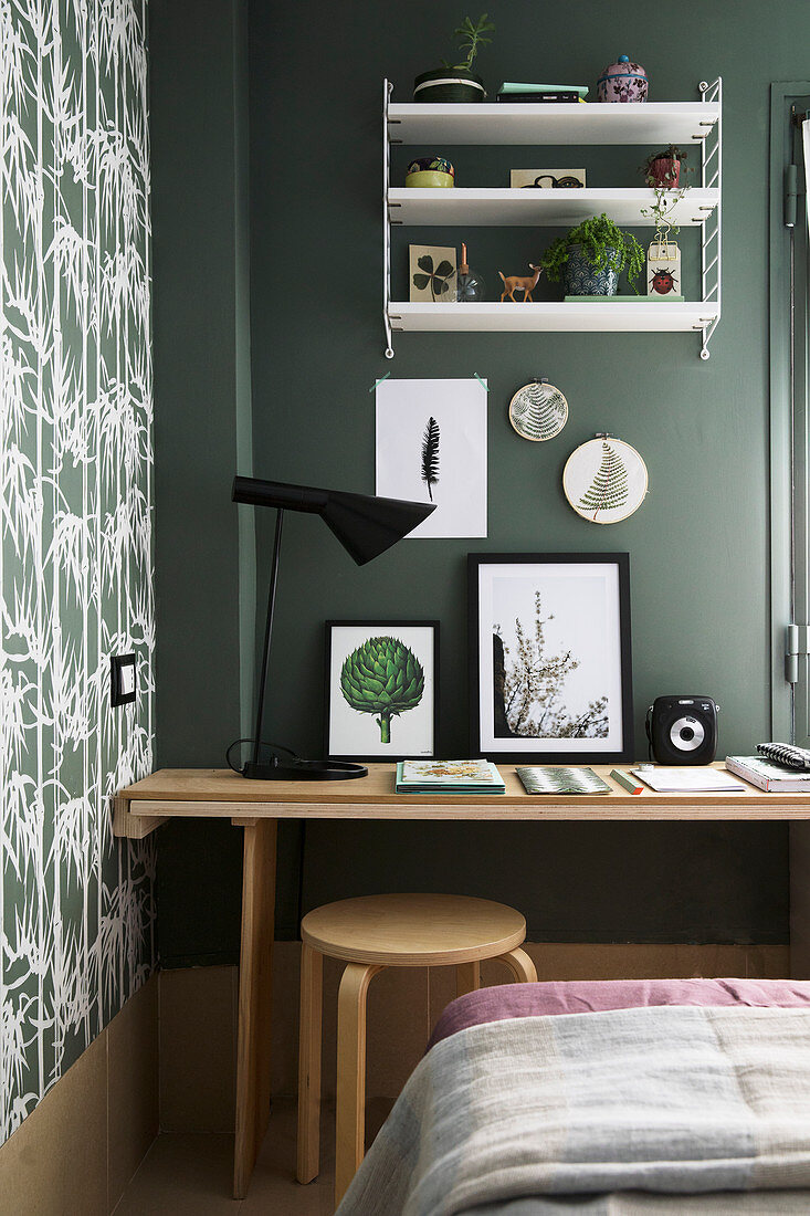 Desk, stool and shelves against green wall in bedroom