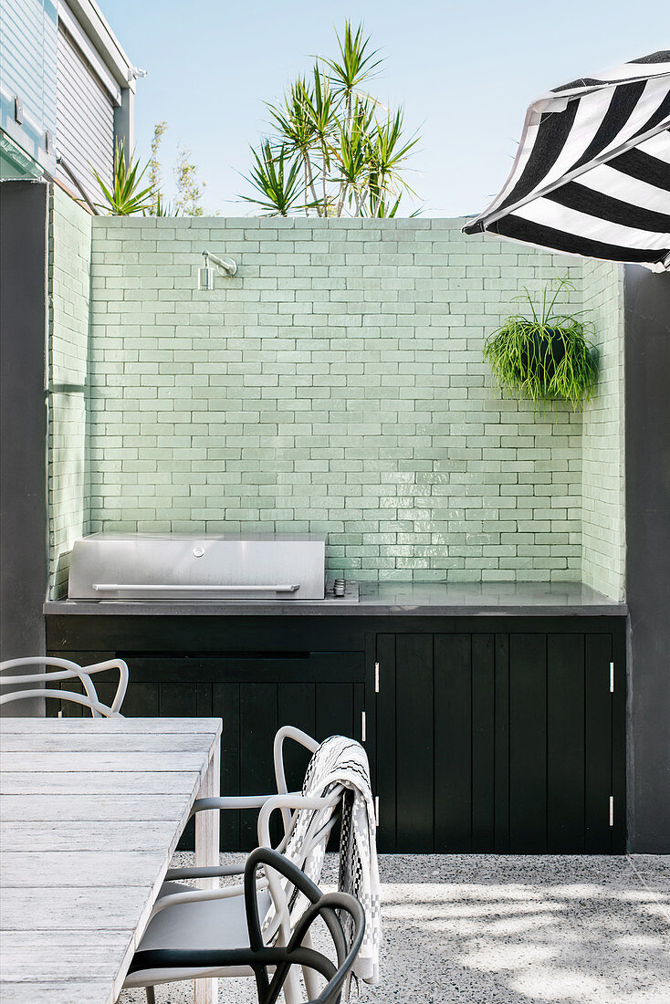 Outdoor kitchen with green, tiled wall on the terrace