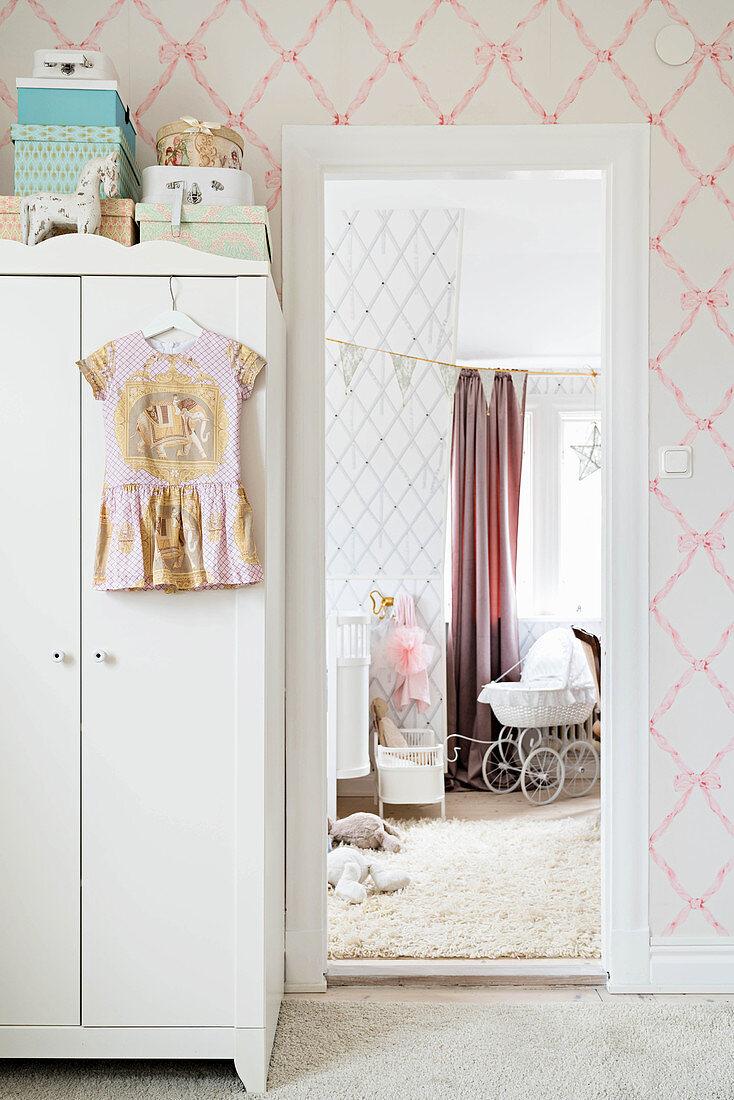 Weißer Schrank mit Mädchenkleid am Türrahmen, Blick ins Kinderzimmer mit Puppenwagen