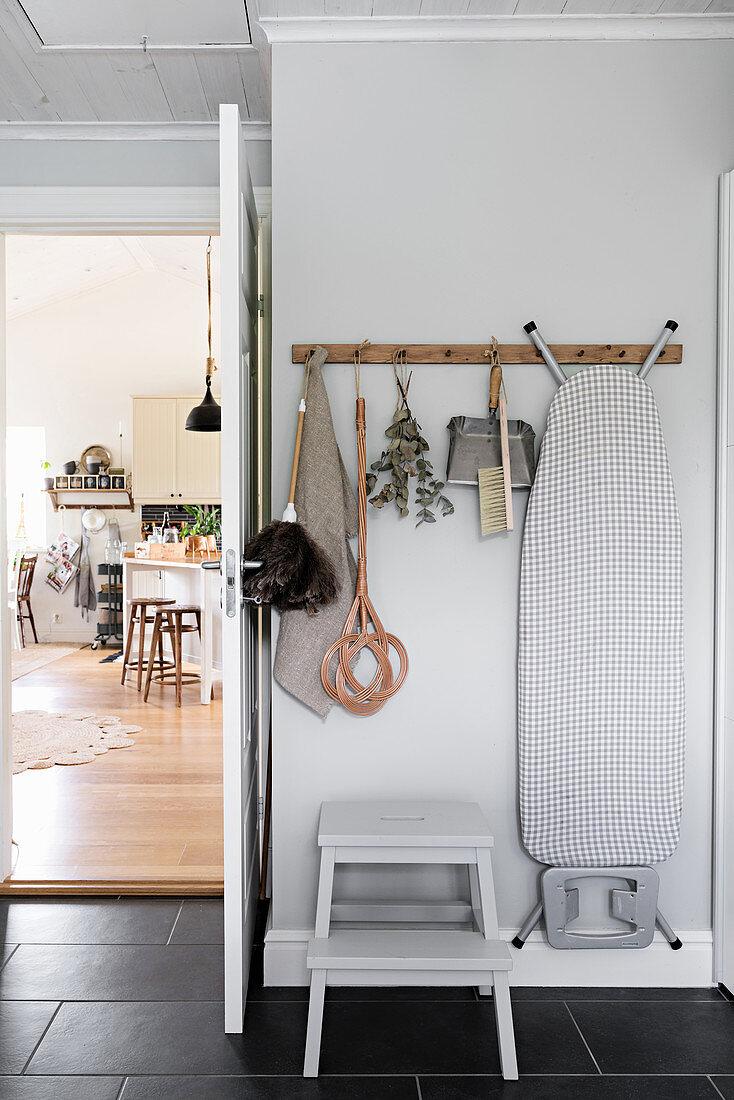Hakenleiste mit Putzutensilien an der Wand hinter der Tür