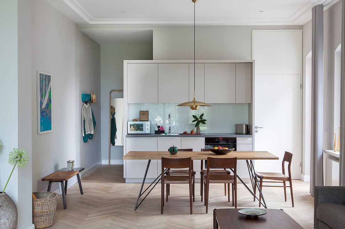 Dining table with slender lines and chairs in front of fitted kitchen in open-plan interior