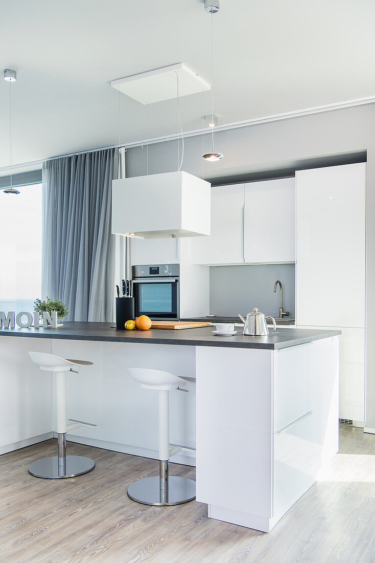White, modern, open-plan kitchen with island counter and barstools