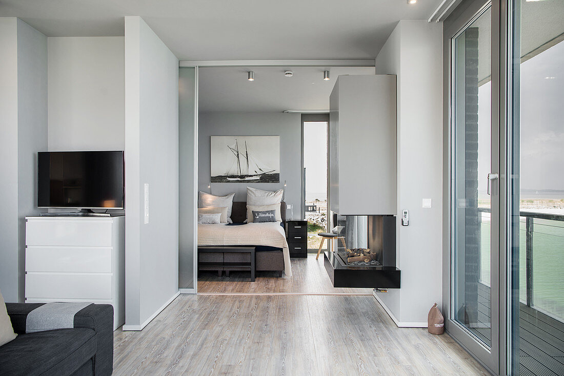 View from living space into bedroom with frosted, sliding glass doors