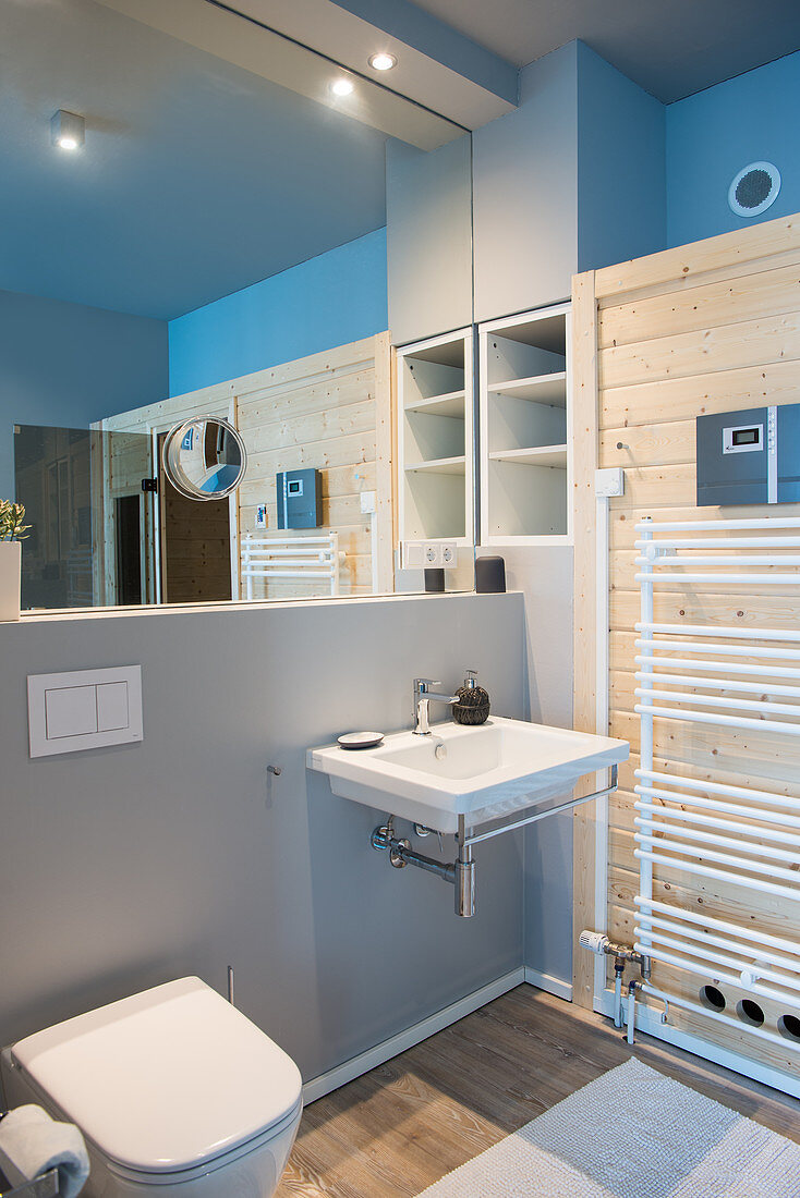 Bathroom with mirrored wall above white sink