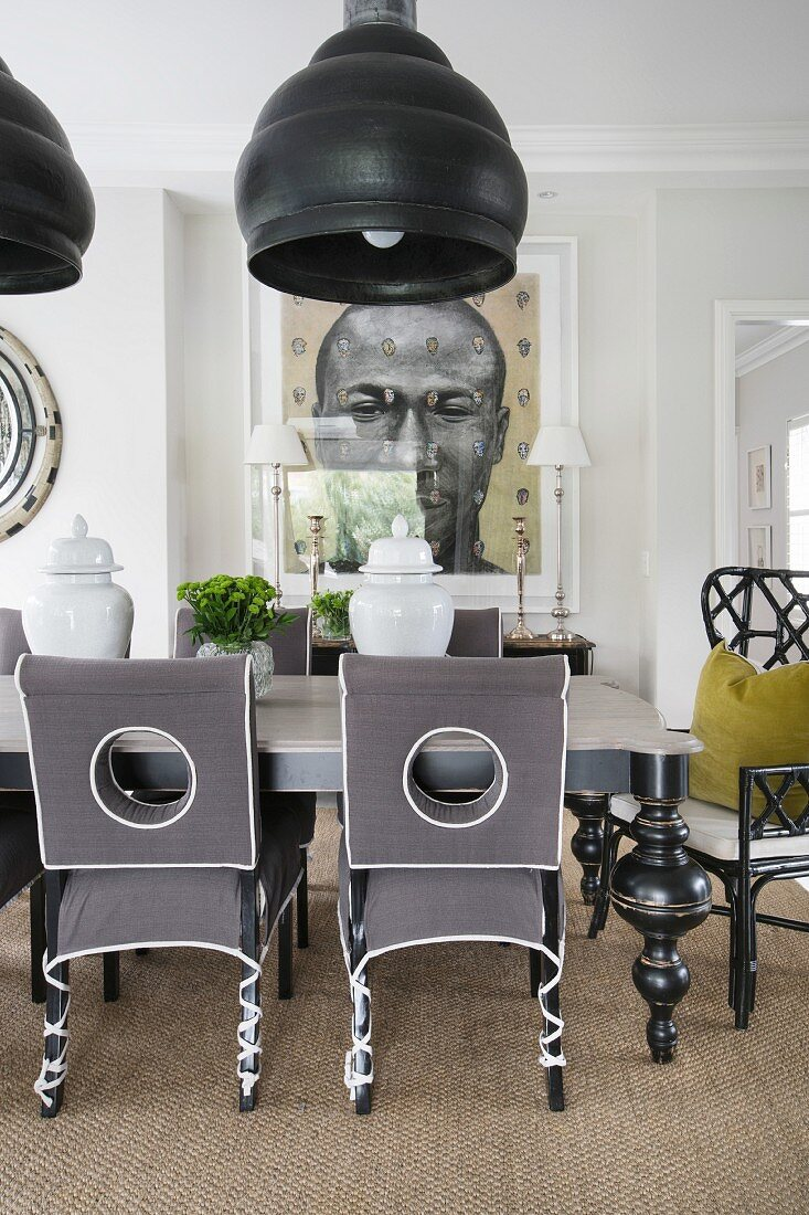 Upholstered chairs and oversized lamps in opulent dining room