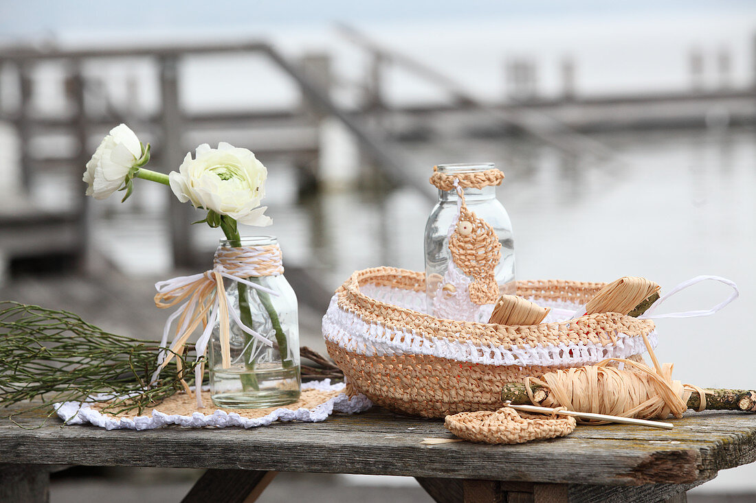 Crocheted raffia bread basket and doily and glass bottle decorated with raffia