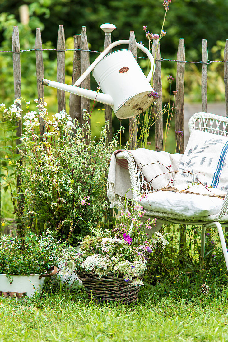 Seating area in front of paling fence decorated with watering can and bouquets of wildflowers