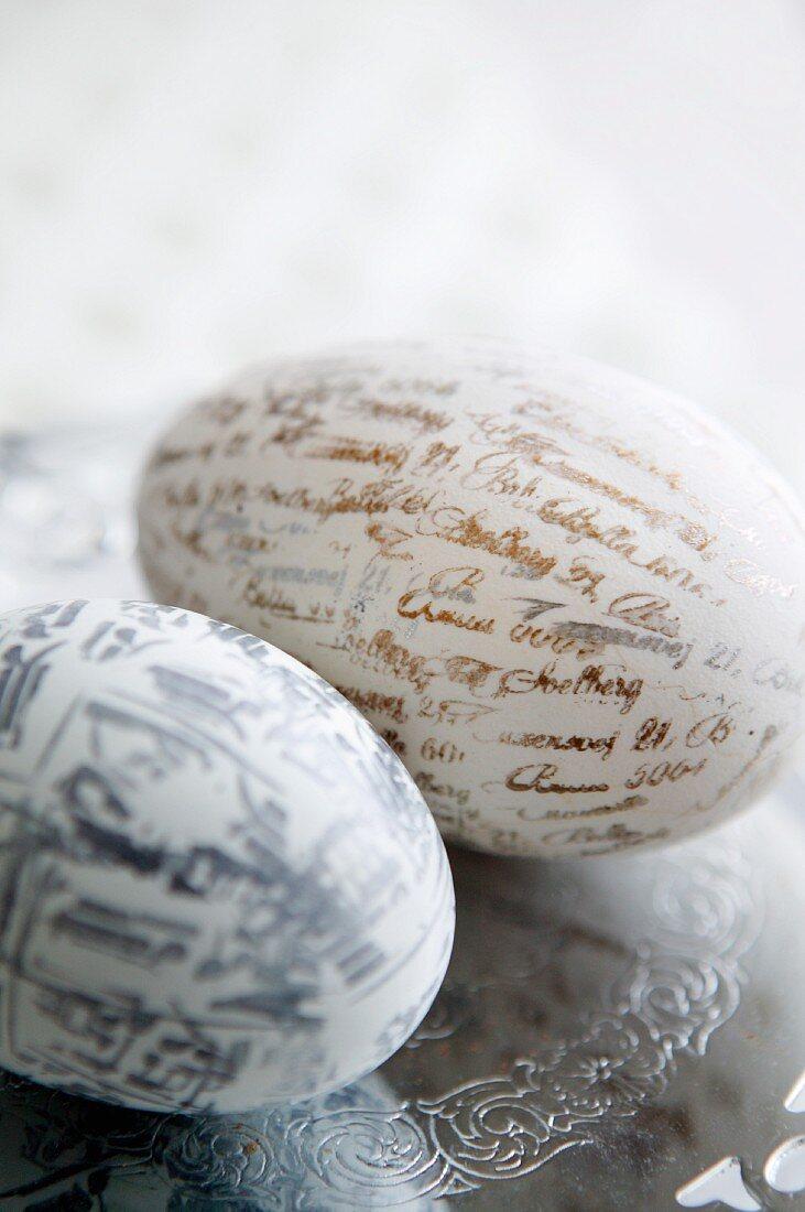 Zwei mit Schriftzügen und Schriftzeichen bedruckte Eier auf Silberteller mit Gravur