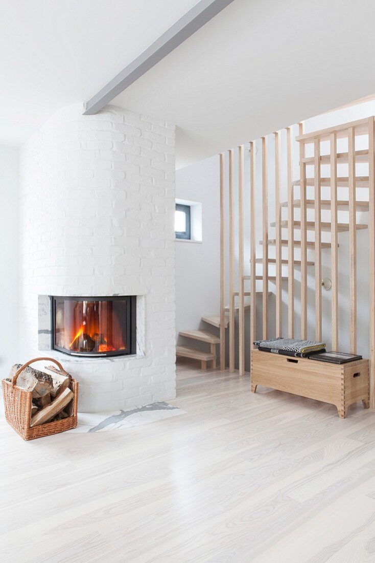 Fire in fireplace with curved glass front at foot of staircase