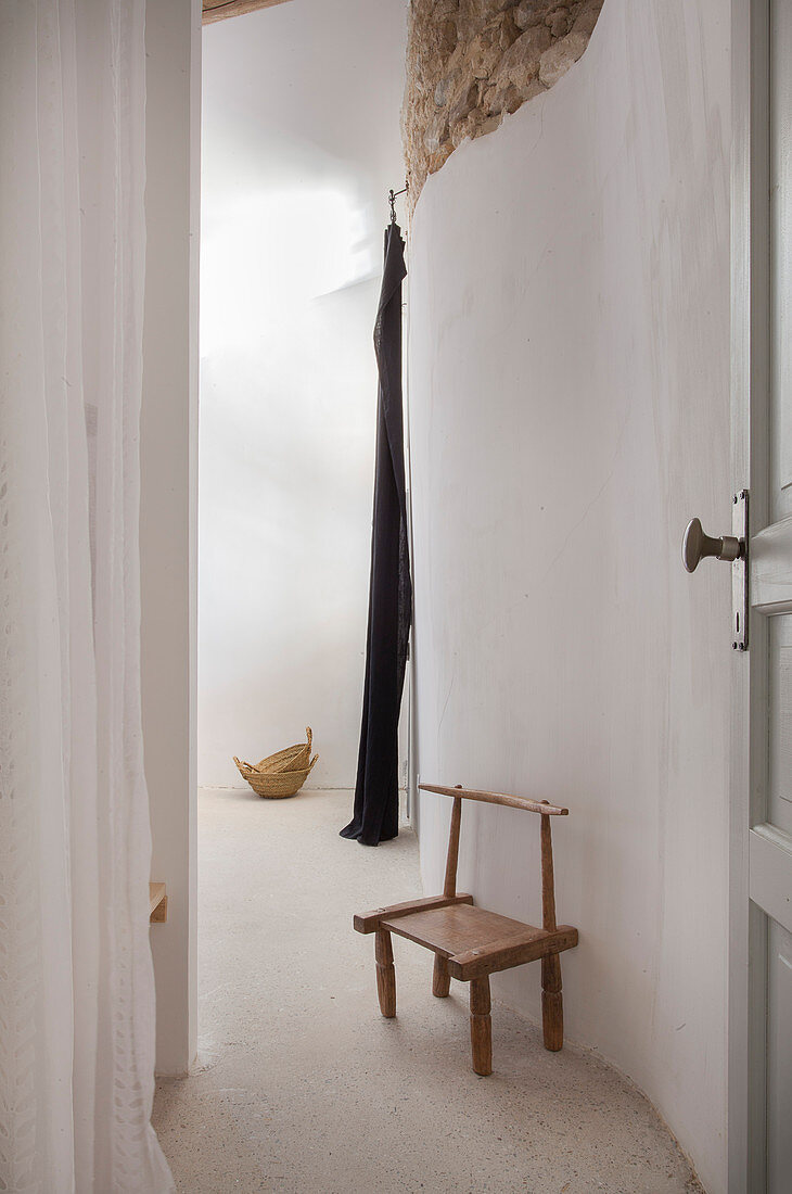 Small wooden chair in hallway with curved walls