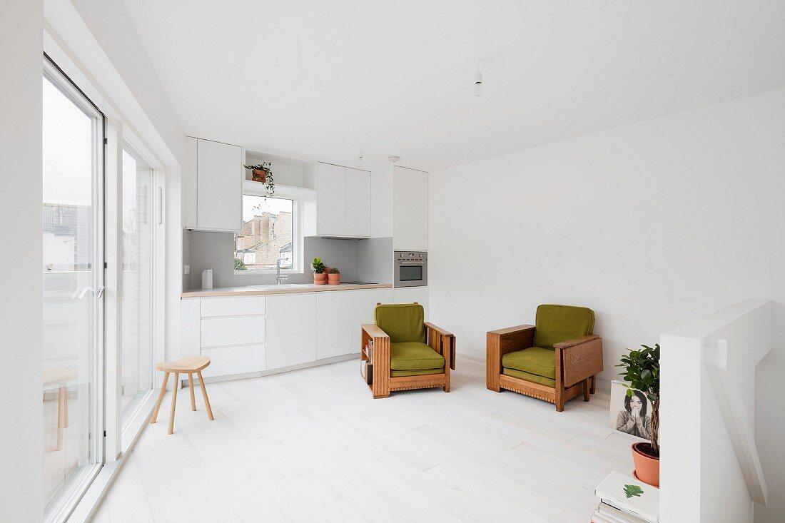 weiße Einbauküche in Dachgeschoss mit Terrassentür, weißem Dielenboden und grün gepolsterten Vintage Sesseln