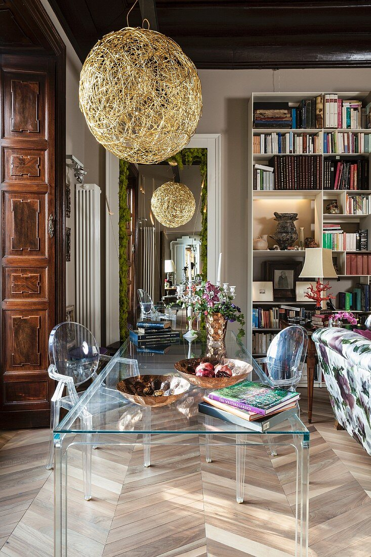 Transparent table and chairs below spherical golden lampshade