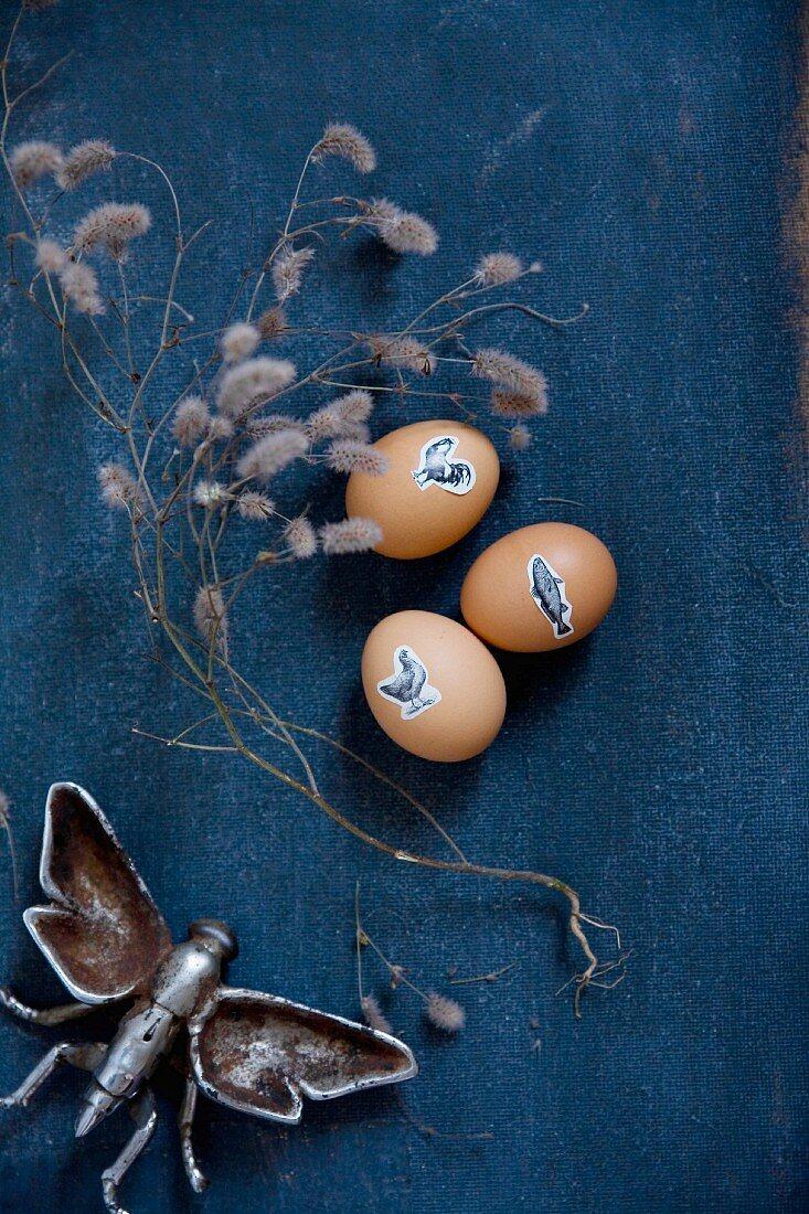 Ostereier mit Tiermotiven dekoriert, Trockenzweig und Insekten-Modell aus Metall auf dunkelblauem Stoff