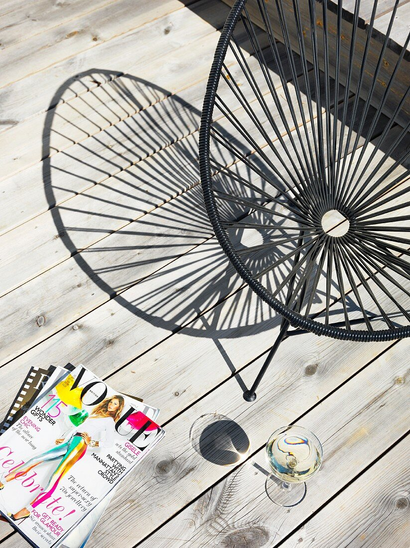 Magazines, glass of wine and black retro chair on wooden terrace
