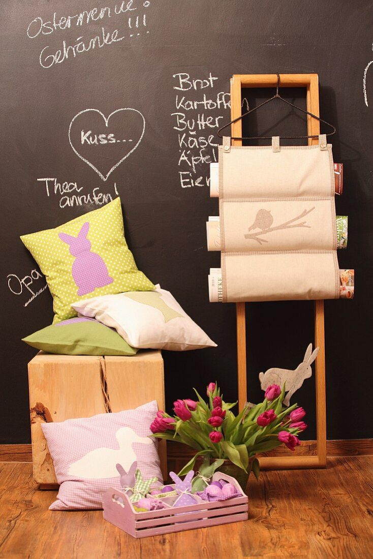 Hand-sewn Easter cushions, magazine rack with wooden frame, vase of tulips and chalkboard wall with messages in chalk