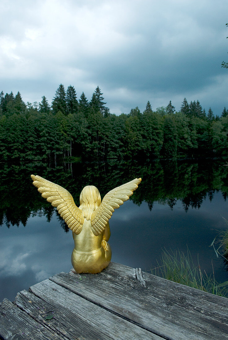 Golden angel figurine sat on jetty next to lake in woods