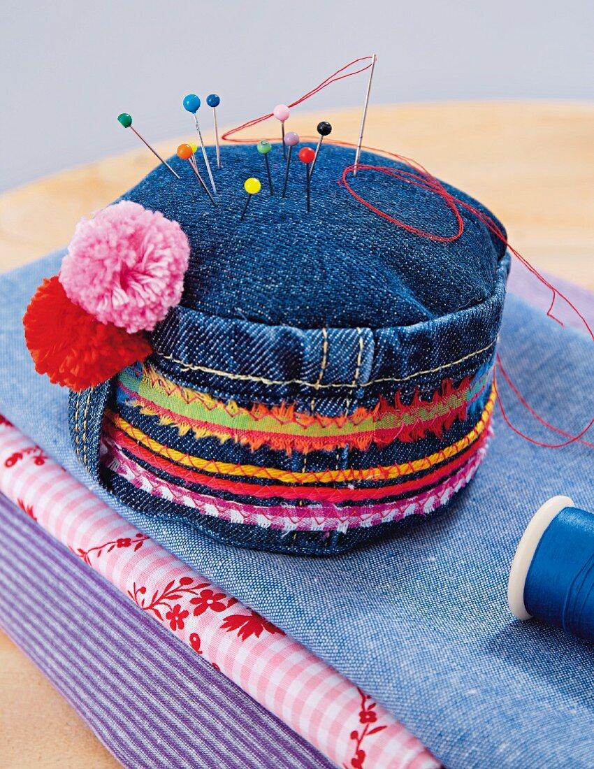 A denim pin cushion with colourful fabric stripes