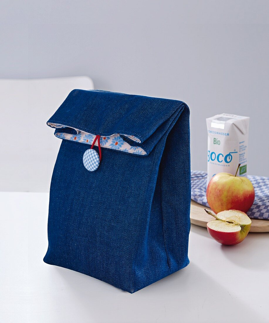 A denim lunch bag with button fastening